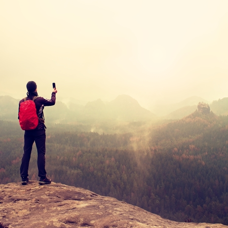 melancholy: Tourist with backpack takes photos with smart phone of rainy vally. Melancholy atmosphere in foggy valley below