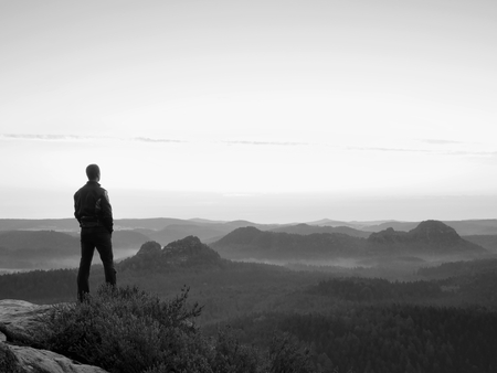 rocky point: Tall man in black on the cliff with heather bush. Sharp rocky mountains park and view point above valley.
