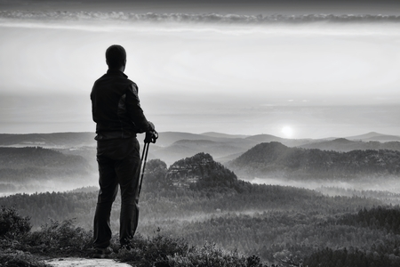 tourist guide: Silhouette of tourist guide with poles in hand. Hiker with sportswear stand on view point above misty valley. Sunny spring daybreak in rocky mountains. Stock Photo