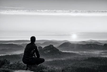 en cuclillas: Runner en sportwear en oscuro en la posición en cuclillas sobre una roca en matorrales de brezo, disfrutar del paisaje