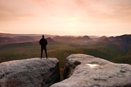 empires: Hiker on the peak of sandstone rock in rock empires park and watching over the misty and foggy morning valley to horizon.