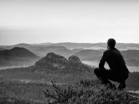squatting: Hiker in black in squatting position on a cliff in heather bushes, enjoy the scenery Stock Photo