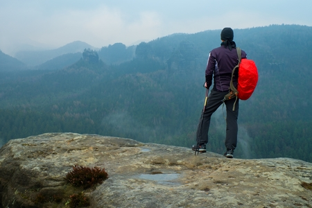empires: Hiker with red backpack on sharp sandstone rock in rock empires park and watching over the misty and foggy spring valley to Horizon.