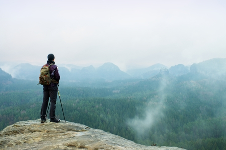 melancholy: Hiker with backpack and poles on cliff rock  watching over the misty and foggy spring valley to Horizon. Melancholy weather.