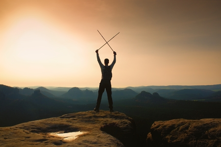 tourist guide: Man with crossed poles above head on cliff.  Foggy  mountain valley bellow. Happy tourist guide with poles in hands. Sunny spring daybreak in hills.