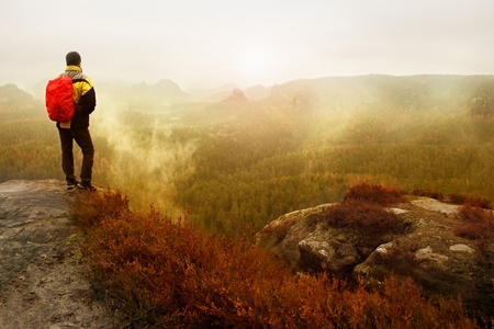 rocky peak: Rear view of male hiker in yellow black jacket on rocky peak while enjoying a daybreak after rainy night above mountains valley