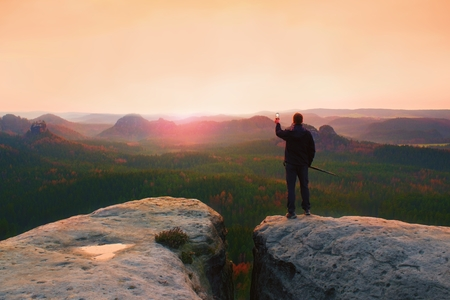 tourist guide: Hiker stand with smart phone on top of mountain and enjoying spring sunrise. Tourist guide with trekking poles. Stock Photo
