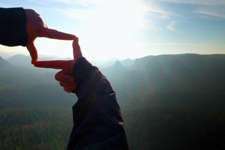 rocky peak: Close up  hands make frame gesture. Blue misty valley bellow rocky peak. Sunny spring daybreak in mountains.
