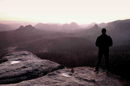 terrain: Man on sandstone rock watching to Sun. Beautiful moment the miracle of nature.
