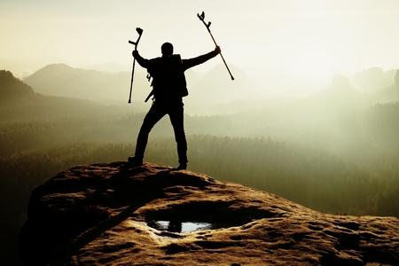 pierna rota: Caminante con la pierna rota en el polo inmovilizador y la medicina por encima de la cabeza alcanz� la cumbre rocosa. Profundo valle brumoso abajo borde afilado. Silueta de los turistas con la mano en el aire. el amanecer de primavera