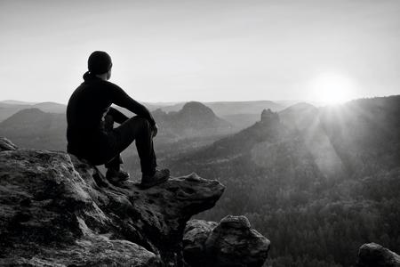 黒のズボン、ジャケットと暗い帽子の大人向け観光崖の端と霧の丘陵の谷の下まで探している上に座る 写真素材