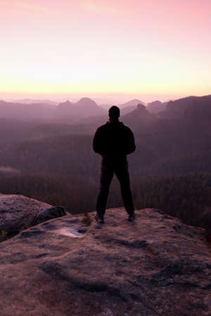 tall man: Tall man in black on cliff and watch to mountain sunrise.Silhouette in selfconfident pose.  Dark silhouette of rocks.