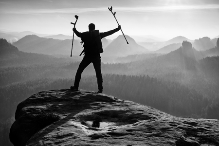pierna rota: Hiker with broken leg in immobilizer. Tourist with  medicine crutch above head achieved mountain peak. Deep misty valley bellow silhouette of man with hand in air. Spring daybreak