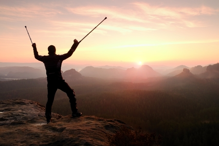 above head: Happy man with broken leg in immobilizer and medicine pole above head stay on peak. Open misty mountain valley bellow cliff. Silhouette of tourist with hand in air. Spring daybreak Stock Photo