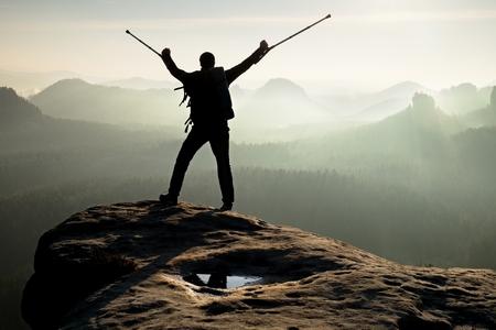 pierna rota: Caminante con la pierna rota en el inmovilizador. Turista con la medicina muleta por encima de la cabeza alcanz� el pico de la monta�a. Profundo valle brumoso abajo silueta del hombre con la mano en el aire. el amanecer de primavera