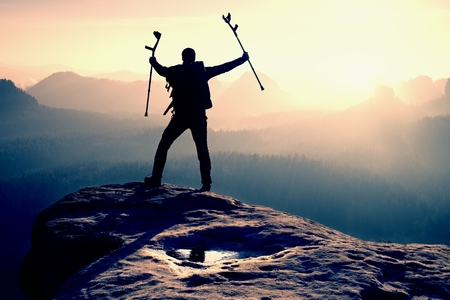surmount: Tourist with  medicine crutch above head achieved mountain peak. Hiker with broken leg in immobilizer.  Deep misty valley bellow silhouette of man with hand in air. Spring daybreak Stock Photo