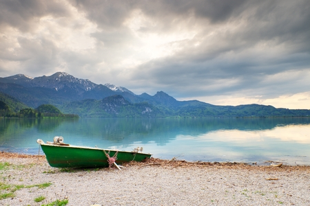Abandoned fishing paddle boat on bank of Alps lake. Morning lake glowing by sunlight. Dramatic and picturesque scene. Mountains in water mirror.