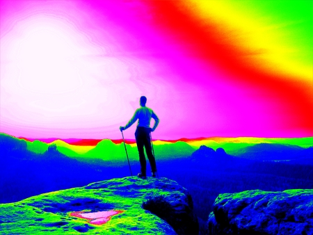 thermography: Fantastic infrared scan. Tourist with poles and big backpack standing on rocky view point and watching into misty morning landscape. Melancholic autumn morning. Thermography colors