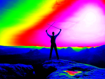 thermogram: Fantastic infrared scan. Tourist with poles and big backpack standing on rocky view point and watching into misty morning landscape. Melancholic autumn morning. Thermography colors