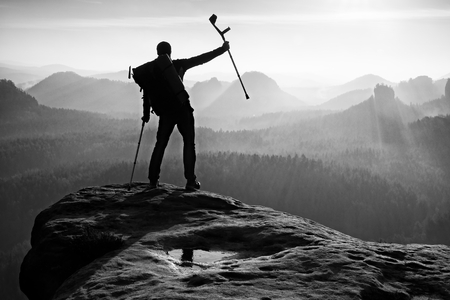 surmount: Happy Hiker with medicine Crutch head above Achieved mountain peak. Hiker with broken leg in immobilizer. Deep misty valley bellow silhouette of man with hand in air.
