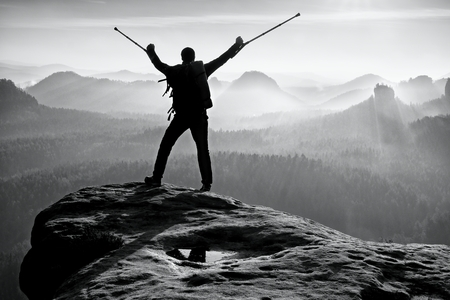 above head: Hiker with broken leg in immobilizer. Tourist with  medicine crutch above head achieved mountain peak. Deep misty valley bellow silhouette of man with hand in air. Spring daybreak