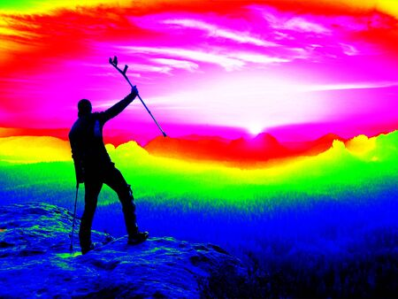 thermography: Infrared scan. Man with broken leg and  crutch  watching into misty morning landscape. Melancholic autumn morning. Thermography colors.