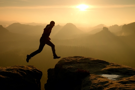 黒の狂気のハイカーは、岩峰の間跳んでいます。幸せな男。素晴らしい夜明けロッキー山脈の深い谷で重いオレンジ霧。自然の奇跡 写真素材