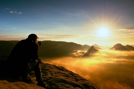 Happy photo enthusiast is  enjoying fantastic miracle of nature on cliff on rock. Dreamy fogy landscape, blue misty sunrise in a beautiful valley below Standard-Bild