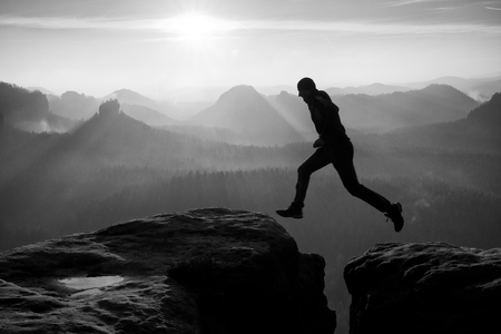 certitude: Hiker in black is jumping between rocky peaks. Amazing activities in rocky mountains, heavy mist in deep valley. Black and white photo
