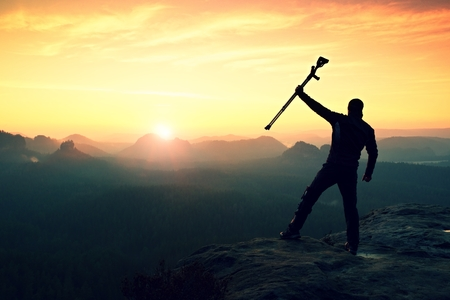 forearm: Tourist with forearm crutch above head achieved mountain peak. Hiker with broken leg in immobilizer and medicine  poles hold hand in air. Colorful misty valley bellow silhouette. Stock Photo