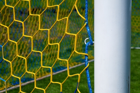 bend over: Hang bended blue yellow soccer nets, soccer football net. Grass and painted white line on football playground in the background
