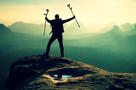 pierna rota: Caminante con la pierna rota en el inmovilizador. Turista con la medicina muleta por encima de la cabeza alcanzó el pico de la montaña. Profundo valle brumoso abajo silueta del hombre con la mano en el aire. el amanecer de primavera