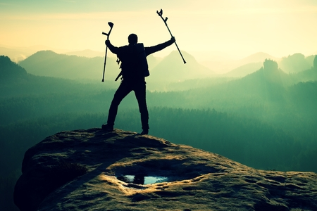 broken hill: Hiker with broken leg in immobilizer. Tourist with  medicine crutch above head achieved mountain peak. Deep misty valley bellow silhouette of man with hand in air. Spring daybreak