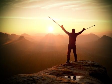 pierna rota: Hombre feliz con la pierna rota la muleta y la medicina. Caminante con la pierna en inmovilizador Lograr la cima de la monta�a. El amanecer brumoso valle silueta abajo.
