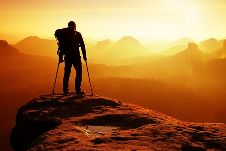 医療松葉杖の頭の上の観光客は、山のピークを達成しました。イモビライザーに足の骨折でハイカー。空気の手を男の深い霧谷怒鳴るシルエット。 写真素材