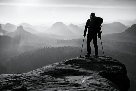 Toerist met been in startonderbreker. Wandelaar silhouet met medicijnen kruk op bergtop. Deep mistige vallei blaten silhouet van de man met de hand in de lucht. Spring dageraad