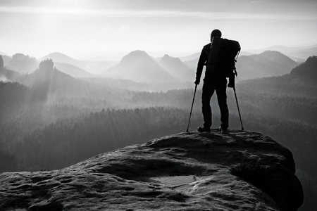 Tourist with leg in immobilizer. Hiker silhouette with medicine crutch on mountain peak. Deep misty valley bellow silhouette of man with hand in air. Spring daybreak