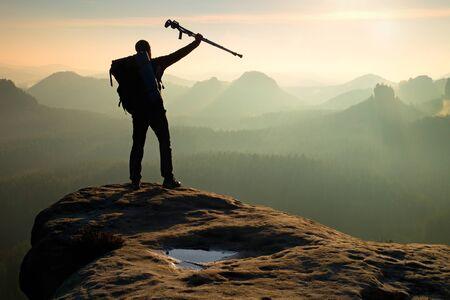 pierna rota: Turista con la medicina muleta por encima de la cabeza alcanzó el pico de la montaña. Caminante con la pierna rota en el inmovilizador. Profundo valle brumoso abajo silueta del hombre con la mano en el aire. el amanecer de primavera
