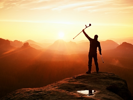 pierna rota: Hombre feliz con la pierna rota y la medicina muleta. Caminante con la pierna en inmovilizador alcanzar el pico de la monta�a. El amanecer brumoso valle silueta abajo.
