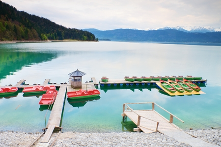 peddle: Empty wooden wharf mole. Blue Alps lake with Rental rowing boats in marina. Wharf for trip ships. Stock Photo