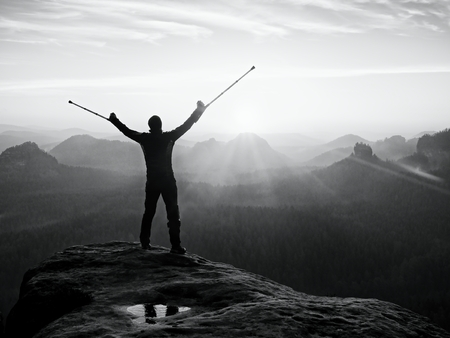 wheater: Tourist with forearm crutch above head achieved mountain peak. Hiker with broken leg in immobilizer and medicine  poles hold hand in air. Colorful misty valley bellow silhouette. Stock Photo