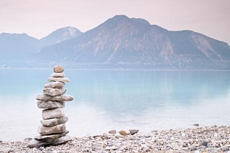 山の湖の青い水の岸にバランスの取れた石ピラミデ。水位ミラーにあるブルーマウンテン山脈。子供が小石からピラミッドを造った。 劣悪な照明条