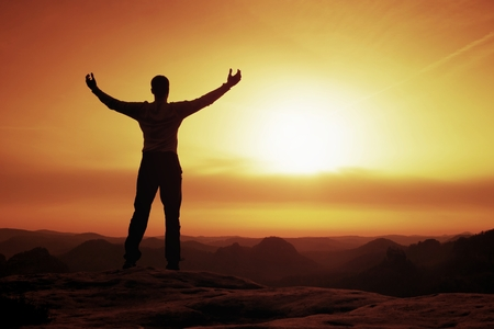 Happy man gesture of triumph with rams in  air. Funny hiker on peak of sandstone rock in national park Saxony Switzerland watching to horizon 版權商用圖片