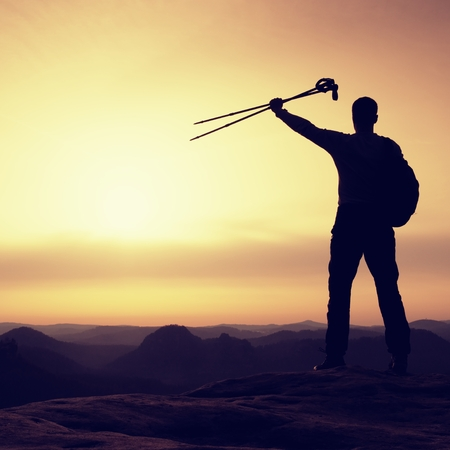 d�livrance: Silhouette of happy tourist with poles in hand above head. Sunny daybreak in mountains. Hiker with sporty backpack stand on rocky view point above misty valley.