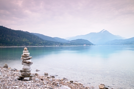 Balanced stone pyramide on shore of blue water of mountain lake. Children built pyramid from pebbles.  Poor lighting conditions.