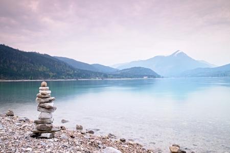 Ausgeglichener Steinpyramide am Ufer des blauen Wasser des Bergsees. Kinder gebaut Pyramide von Kieselsteinen. Schlechte Lichtverhältnisse.