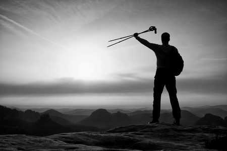 délivrance: Silhouette of happy tourist with poles in hand above head. Sunny daybreak in mountains. Hiker with backpack sports stand on rocky view point above the misty valley.