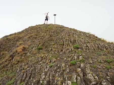 basalt: Tourist on sharp peak of basalt formation. Long basalt poles of cold volcano.