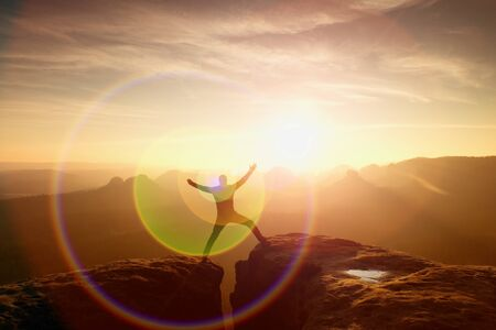 strong light: Strong light reflection in lens. Jumping hiker in black celebrate triumph between two rocky peaks. Wonderful daybreak.