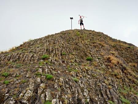 basalt: Tourist on sharp peak of basalt formation. Long poles of cold basalt volcano.